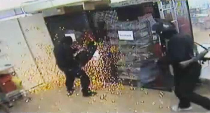 Masked man cutting through locks during a Swedish bank heist